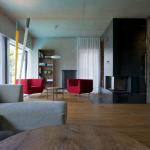 Neutrální barevné pojetí interiéru oživují červená křesla.