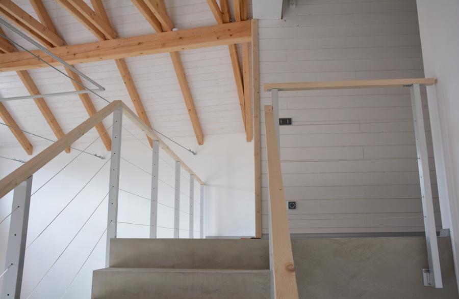 Schodiště s betonovou stěrkou zjemňují okolní materiály.