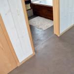 Betonová stěrka použitá na podlaze v chodbě i koupelně je doplněna dřevěnými detaily. Všimněte si dřevěného obložení vany.