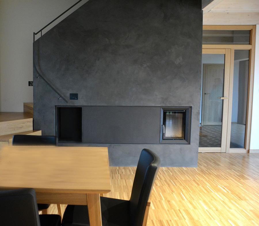 Komínová stěna je zviditelněná šedou betonovou stěrkou. Prostor díky ostatním použitým materiálům působí zabydleně.