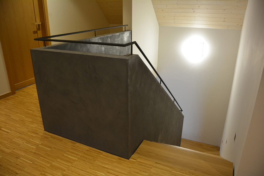 Dřevěné schodiště doplněné zděným zábradlím zvýrazněným betonovou stěrkou.