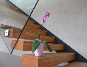 Betonová stěrka se často používá na stěnách u schodiště. Ideálně dřevěného.