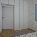 Kolem dveří v ložnici byla navržena sestava skříní na míru prostoru.
