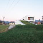 Střecha domu porostlá zelení splývá s okolním prostředím.
