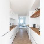 Bílá kuchyně je oživena dubovými fošnami.