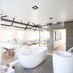 Elegantní koupelna je díky stěně z čirého skla optickou součástí polyfunkčního prostoru