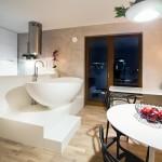 Vana je umístěna na pódiu mezi kuchyňskou linkou a obývací částí pokoje. Netradiční je také lustr pokrytý rostlinami.