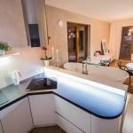Od obývacího prostoru odděluje kuchyň podsvětlený pult