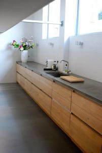Betonová deska s textilní tkaninou v kombinaci s dřevěnými skříňkami nepůsobí výrazně studeně.