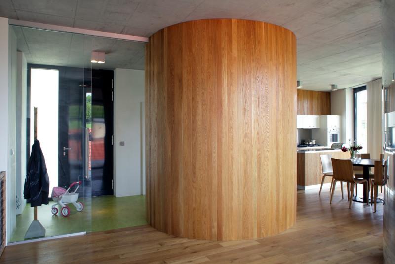 Studený betonový strop je zjemněn dřevěným obkladem části stěny.