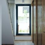 V úzké chodbě jsou navrženy posuvné dveře, které šetří prostor.