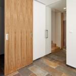 Velkorysá vstupní hala. Za dřevěnými posuvnými dveřmi se nachází šatna.