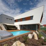 Obě dvoupatrové hmoty domu kompozičně vyvažuje výškové uspořádání zahrady s přírodními prvky.