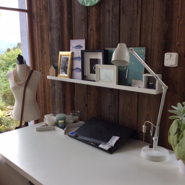 Stěna za stolem je obložená ošetřeným dřevem. Tento prvek vnáší do pokoje výraznou přírodní atmosféru.
