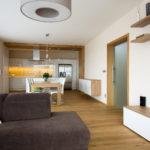 Kuchyně je opticky oddělena dřevěným pásem obloženým na stěně i stropu.