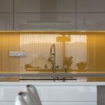 Bílá kuchyně je rozzářena žlutým sklem mezi horními a spodními skříňkami.