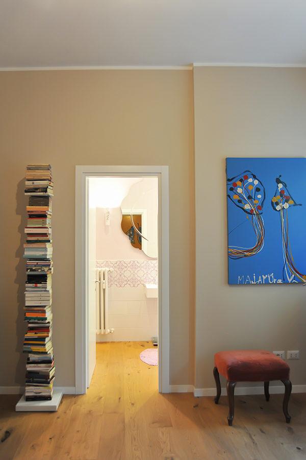 V bytě nechybí nápadité dekorace. Třeba jako stoh knih vedle dveří.