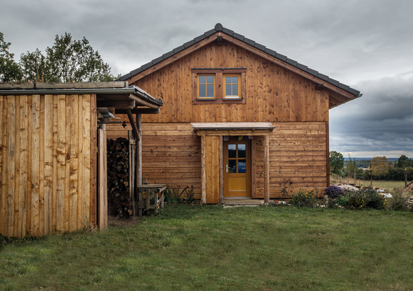 Střechu této dřevostavby pokrývají solární panely, kterými rodina získává potřebnou elektrickou energii.