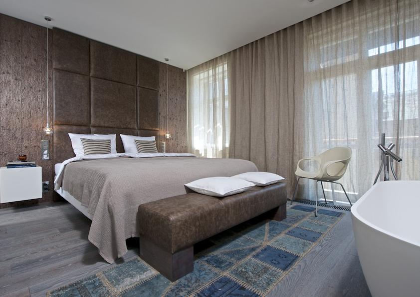 Tato ložnice není vyjímečná jen vysokým čelem postele, ale i umístěním vany, která je hned před ní.