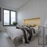 Čelo postele je součástí šatní skříně, která je navržena na míru celé stěny. Ve výklenku nechybí LED osvětlení.