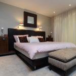 Koberec a závěsy ložnici zútulňují. Jejich světlé odstíny jsou kontrastní k tmavému rámu postele.