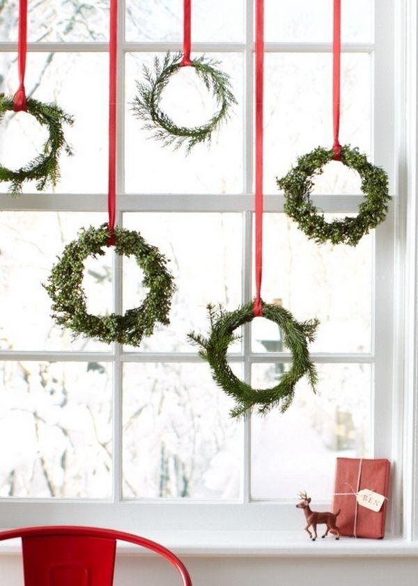 V bílých oknech se budou pěkně vyjímat věnečky z větviček. Upozornit na ně můžete červenou stuhou.