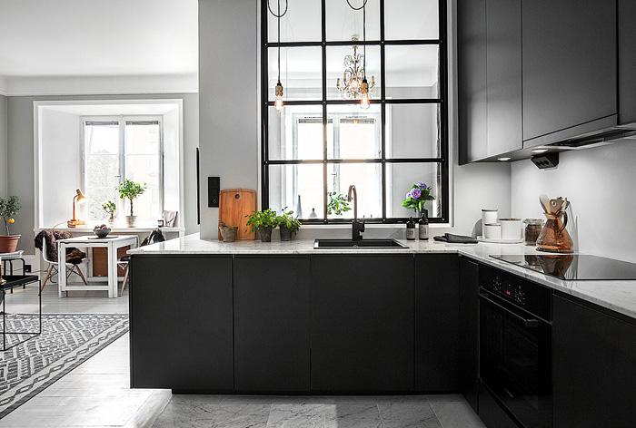 Černá kuchyně v matném provedení a k tomu elegantní pracovní deska s nízkou tloušťkou, která plynule přechází i mezi horní a spodní skříňky.