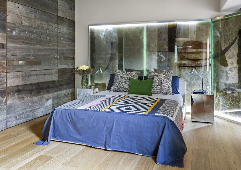 Za zády postele je za sklem výtvarné dílo od Vasudha