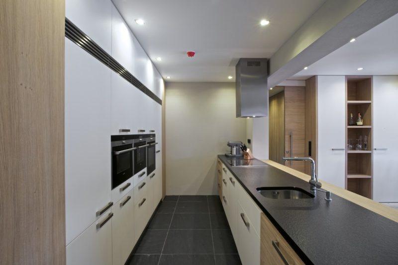 Vestavěné kuchyňské skříně slouží jako spíž, pro úschovu nádobí a vešly se i spotřebiče. Pracovní deska z jednoho kusu materiálu je elegantní.