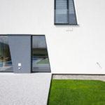 Kompozici ploch na fasádě odpovídá i uspořádání zpevněných ploch a travnatých na zahradě.