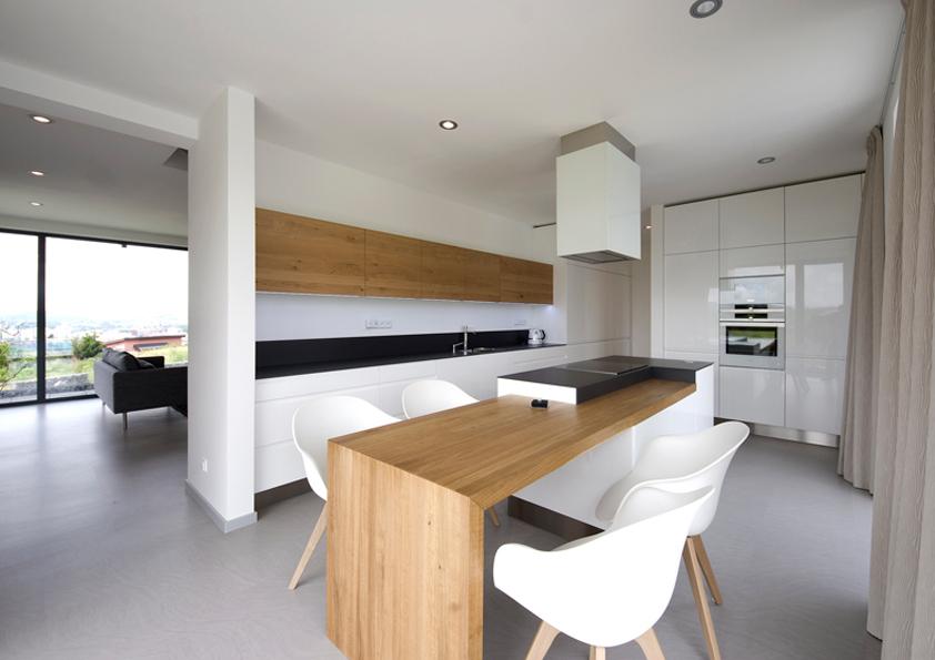 Kuchyně s jídelním stolem je opticky oddělena od společenské místnosti.