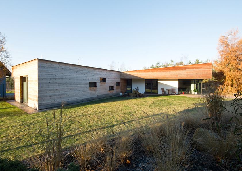 Jednoduché tvary hmot domu jsou harmonicky dokomponovány střídáním obložených a omítnutých ploch s velkorozměrovými okny.