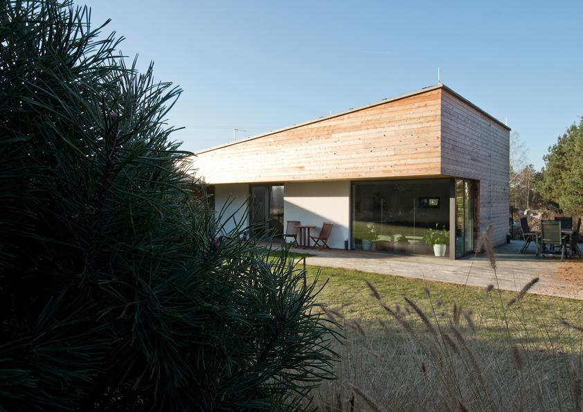 Na fasádě křídla s pultovou střechou spolupůsobí mimo kontrastu obložených a bílých stěn také hra světla a stínu.