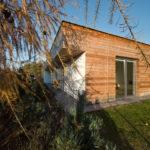 Jednoduchý štít obytného křídla rodinného domu má dřevěný obklad, prolomený dvoukřídlovým vysokým oknem.