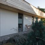Kompozice řešení fasády vychází ze střídání vodorovného členění dřevěného obkladu římsy pultové střechy a svislých pásů vysokých oken a plných zděných bílých pilířů.
