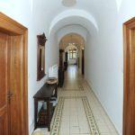 Zrekonstruovaná vstupní chodba. Na dlažbě je uplatněn historizující kobercový vzor. Dřevěné ostění dveří je klasicistní replikou jiných dveří v přízemí.