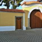 Zrekonstruovaná vstupní brána s vraty, doplněna o chybějící boční zdivo a obloukovou šambránu.
