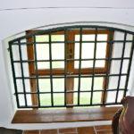 Okno s novou ochrannou mříží na podestě výstupu na půdu. Mříž je tvarově přizpůsobena dobovému výrazu.