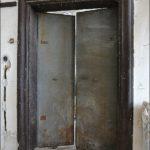 Dveře z haly do ložnice v 1. patře před renovací, kdy bylo nutno mimo jiné odstranit novodobé nevhodné oplechování.