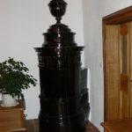 Klasicistní kamna po celkovém zrestaurování. Rozbité části byly odborně doplněny, horní váza byla postavena do původní polohy na stopku.