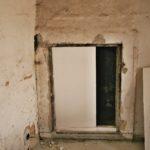Pohled před rekonstrukcí na otvor do topné komory bez dveří v hale v 1. patře.