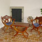 Zrekonstruovaná hala v 1. patře s pohledem na dveře do původních topných komor. Na podlaze jsou osazeny zrenovované půdovky, sedací nábytek je původem z Indonésie.