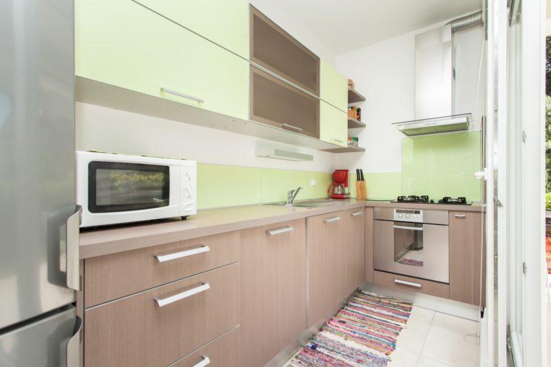 Horní skříňky v úzké kuchyni by měly mít otevírání nahoru, takzvané klopny.