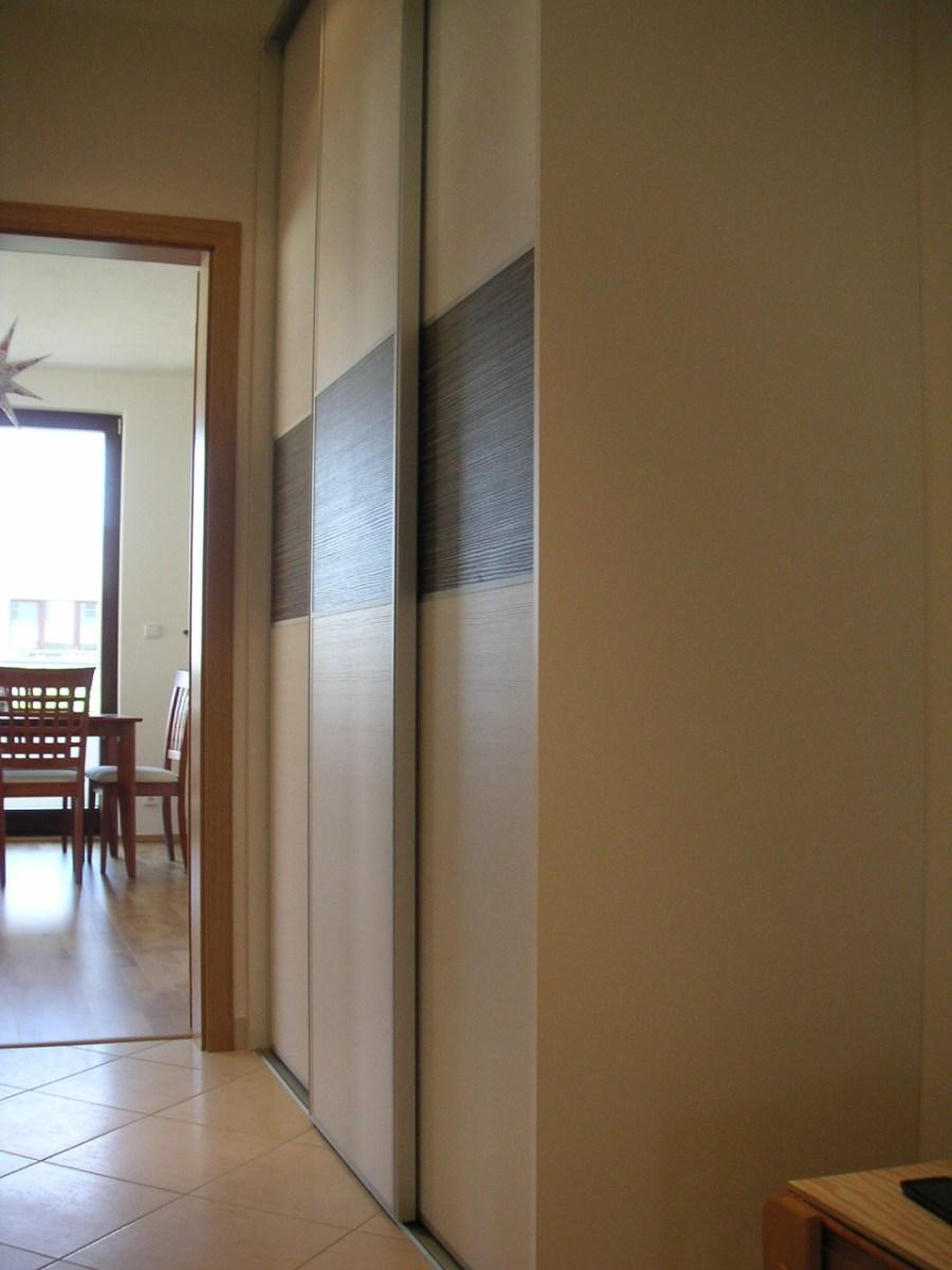 Výhodou vestavěné skříně je, že pojímá věci přes celý rozměr stěny