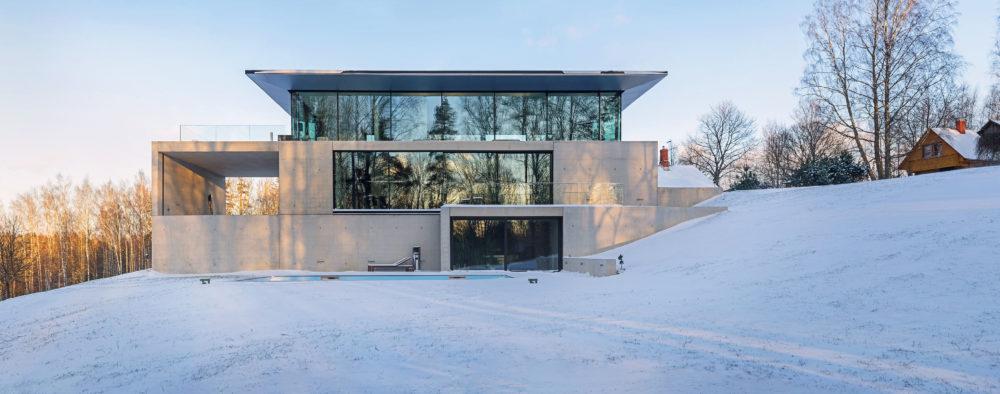 """Architekti studia OUTOFBOX tomu říkají """"asketický design"""". Impozantní budova ze skla a betonu organicky zapadá do terasovitého terénu."""