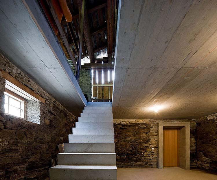Ačkoli to zvenku nevypadá, i stodola prošla náležitou rekonstrukcí. Stropní podhled je stejně jako schodiště ze železobetonu. V pozadí je vstup do podzemního tunelu spojujícího stodolu s domem.